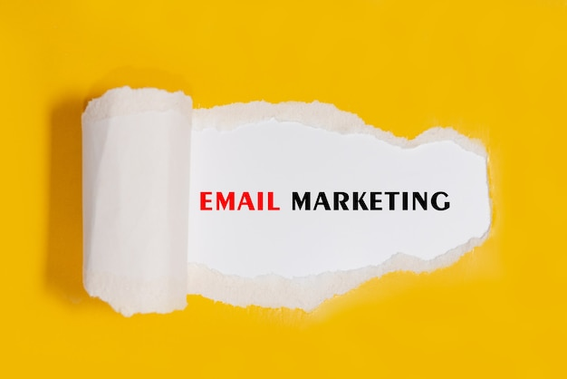 Torn paper with word email marketing - business concept