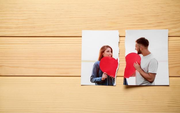 Разорванное фото счастливой пары на деревянной поверхности. понятие развода