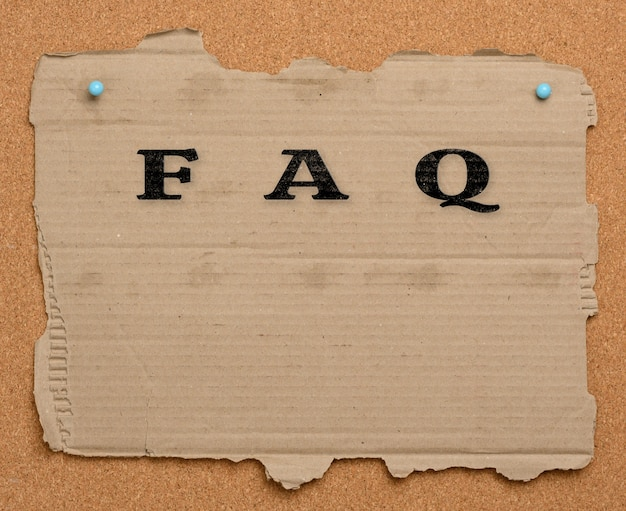 A torn piece of brown cardboard paper is pinned to a corkboard. inscription faq, search for answers to questions, help in navigation