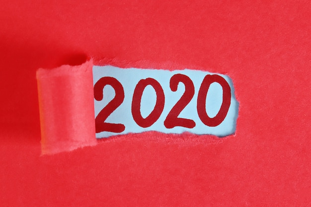 Torn piece paper revealing word new year 2020. new year planing. 2020 goals.