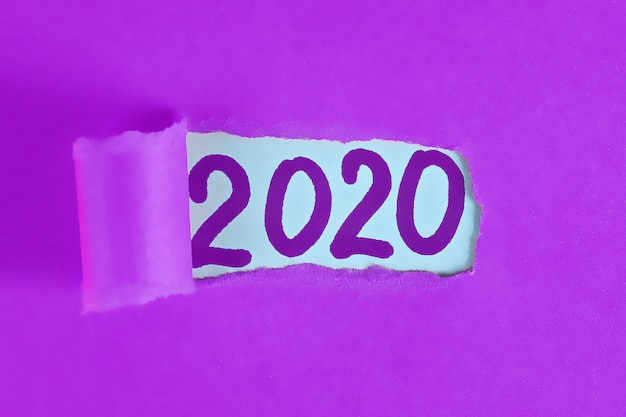 Torn piece paper revealing word new year 2020.