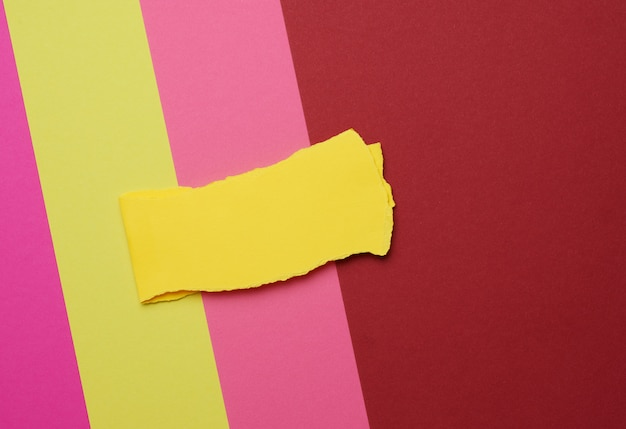 Torn piece of yellow paper on a colored space, abstract backdrop