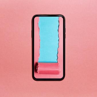スマートフォンの画面にシアン色のテキスト用のスペースがある破れたピンクの紙。パステルピンクの質感。