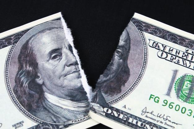 Разорванный разорванный обесцененный банкнот за сто долларов. обвал доллара. девальвация. падающая валюта