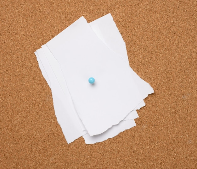 Torn white blank white sheet of paper affixed with a plastic button on a brown cork board