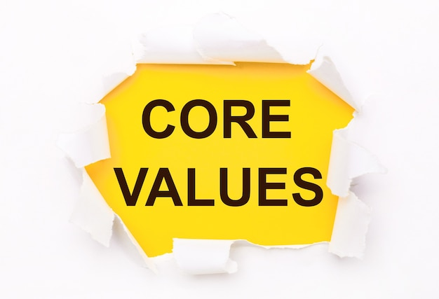 Torn white paper lies on a bright yellow background with the text core values