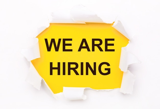 Torn white paper lies on a bright yellow background with the text we are hiring