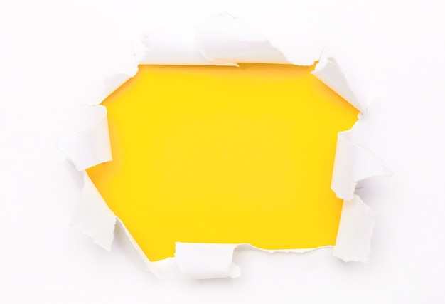 Torn white paper lies on a bright yellow surface. copy space