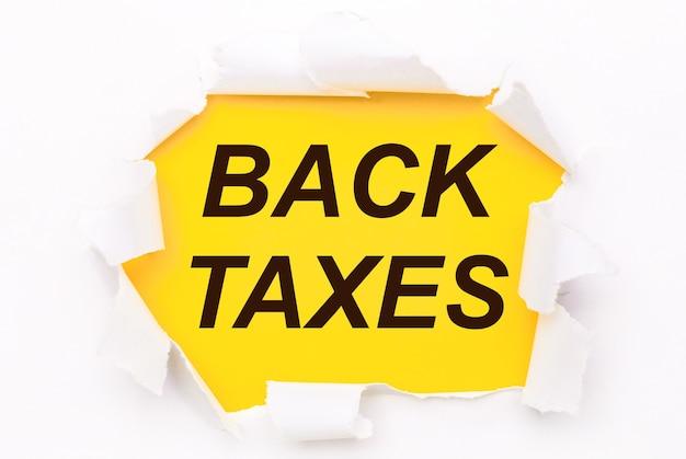 Рваная белая бумага лежит на ярко-желтом фоне с текстом «налоги назад».