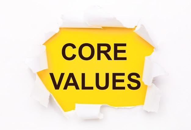 Рваная белая бумага лежит на ярко-желтом фоне с текстом основные ценности.