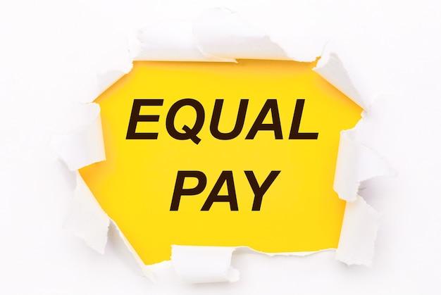 Рваная белая бумага лежит на ярко-желтом фоне с текстом equal pay.