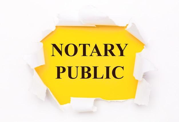 Рваная белая бумага лежит на ярко-желтом фоне с текстом «нотариус».