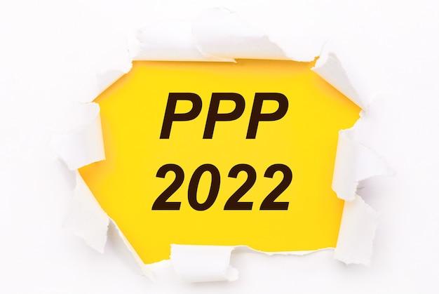 Рваная белая бумага лежит на ярко-желтом фоне с текстом ppp 2022