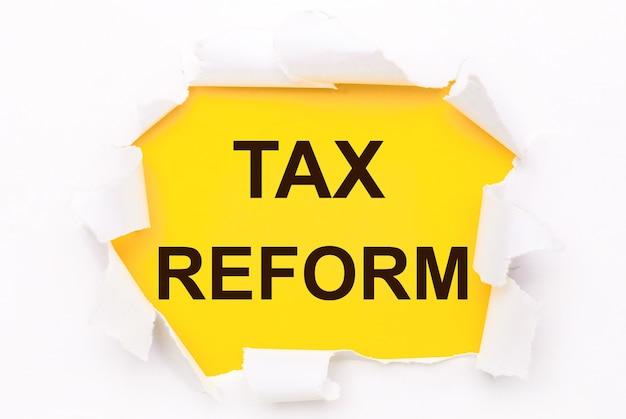 Рваная белая бумага лежит на ярко-желтом фоне с текстом налоговая реформа.