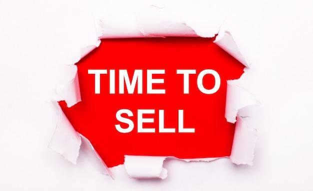 Рваная белая бумага лежит на красном фоне. на красном цвете текст белый время продать