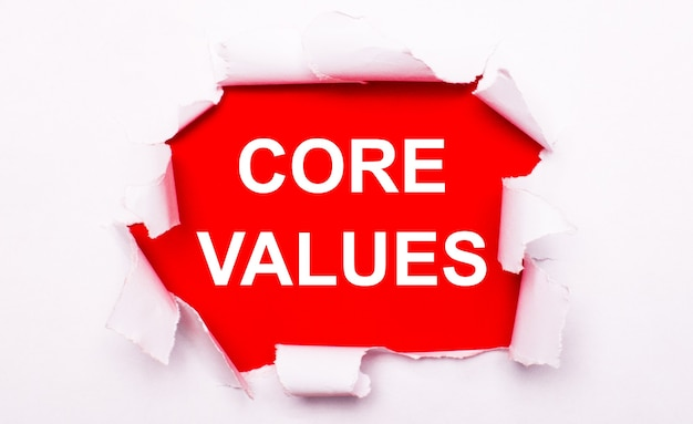 Torn white paper lies on a red background. on red, the text is white core values