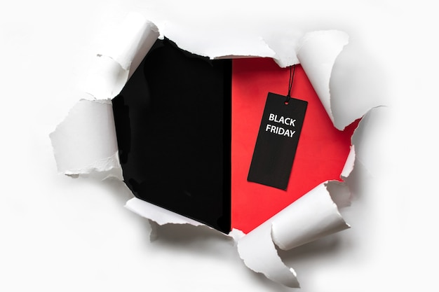 블랙 프라이데이 가격표가 있는 빨간색과 검은색 배경에 찢어진 백서. 텍스트를 위한 공간 복사