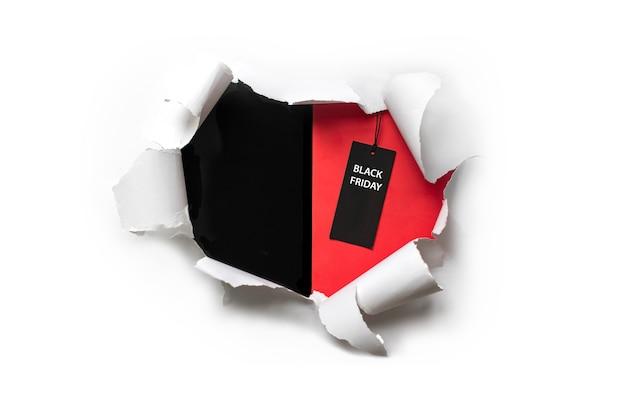 ブラックフライデーの値札が付いた赤と黒の背景に破れた白い紙。テキスト用のスペースをコピーする