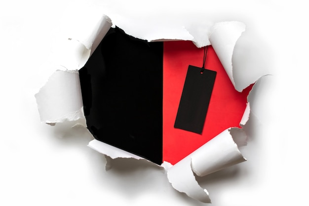 Torn white paper on a red and black background with a black friday price tag. copy space for text