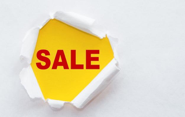 Рваная белая бумага со словом распродажа! скидки и акции