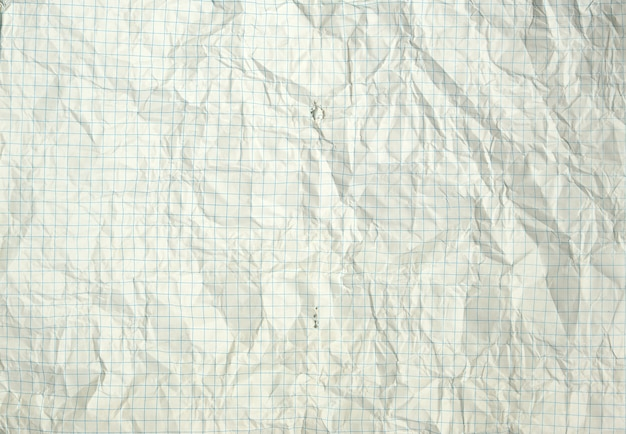 Torn and wrinkled white blank squared sheet from a school notebook background