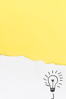 Torn yellow paper with hand drawn light bulb on white background