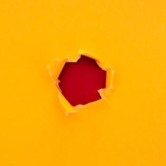 赤い段ボールの背景にテキスト用のスペースと引き裂かれた黄色い紙