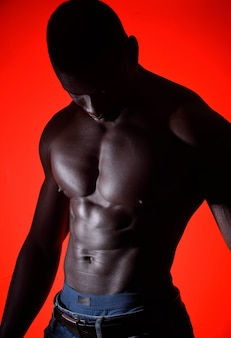 Torso of an african man on red background