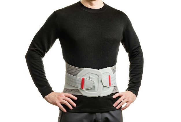 The torso of a man in an orthopedic corset on a white wall.