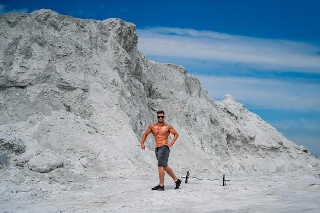 バーベルウェイトを持つ上半身裸の男の胴体。ボディービルとアウトドアスポーツのコンセプト。採石場での写真撮影。