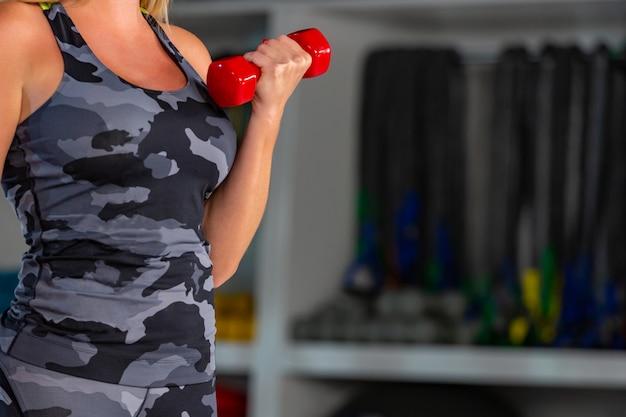 ダンベルを持ち上げる若いフィット女性の胴体