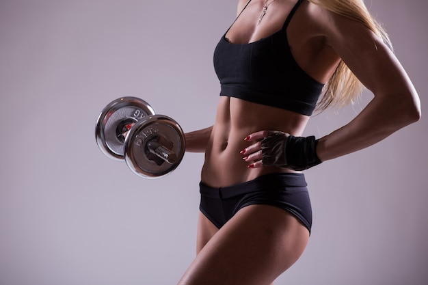 Torso of a young fit woman lifting dumbbells isolated on white wall
