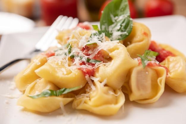 접시에 토마토 소스를 곁들인 토르텔리니를 닫습니다.