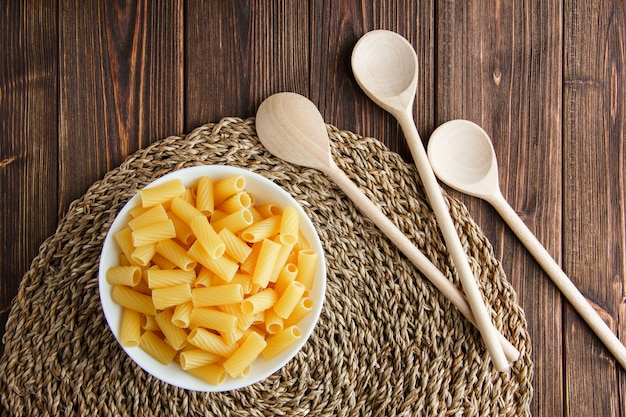 Tortiglioni pasta in a bowl with wooden spoons flat lay on wooden and wicker placemat