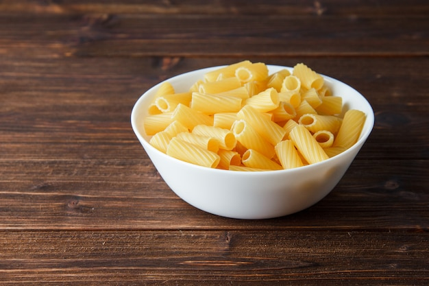 Tortiglioni pasta in a bowl on a wooden table. high angle view.