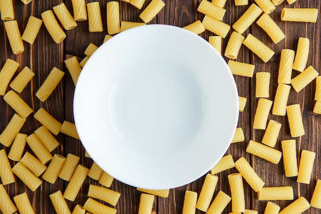 Tortiglioni pasta with empty plate flat lay on a wooden table