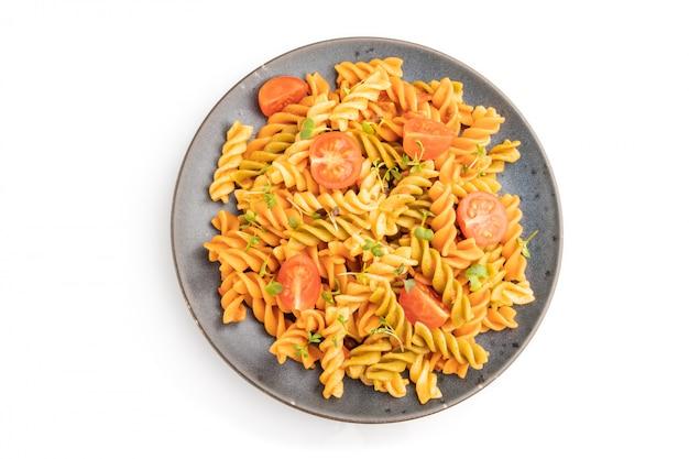 Tortiglioniセモリナパスタトマトと白いテーブルの上のマイクログリーンスプラウト。
