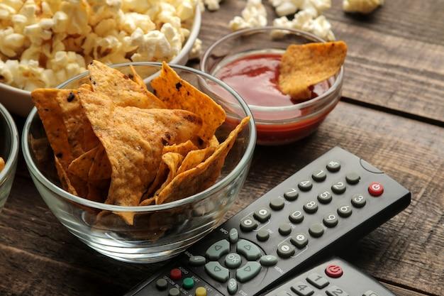 토르티야와 팝콘, 갈색 나무 배경의 tv 리모컨. 집에서 영화를 보는 개념. 확대.