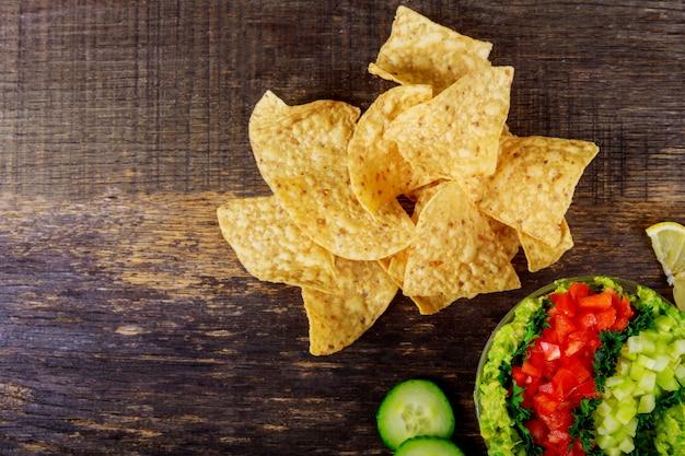 Tortilla chips, avocado dip, tomato and cucumber