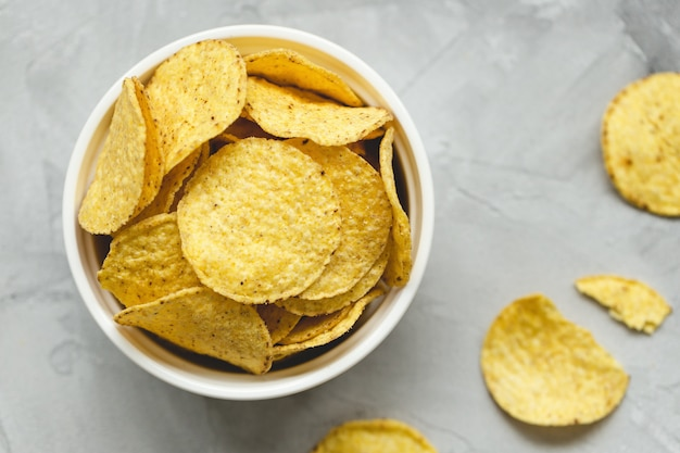 Tortilla corn chips in bowl on a gray background