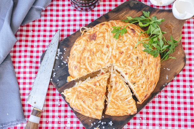 Тортилья де фидео по-испански или омлет с лапшой, порционированный на деревянной доске. с высоты птичьего полета. возьмите пейзаж. крупный план.