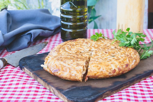 Тортилья де фидео по-испански или омлет с лапшой, порционированный на деревянной доске. нормальный вид. возьмите пейзаж.