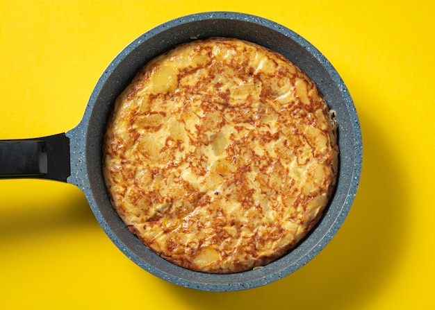 Tortilla de patatas on skillet on yellow, typical spanish dish.