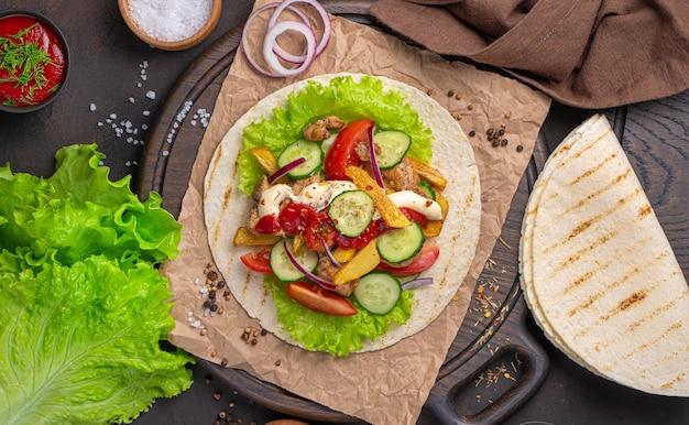 木の板にトルティーヤ、肉、フライドポテト、新鮮な野菜、ソース。メキシコのタコス。上面図。