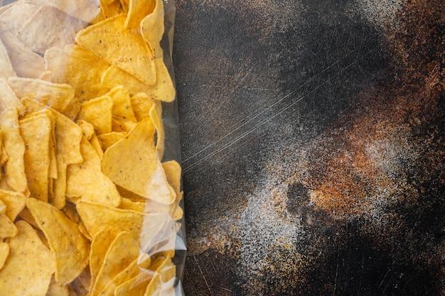 토르티야 멕시코 나초 칩은 비닐 봉지에 든 오래된 어두운 전원풍 배경, 위쪽 전망 또는 텍스트 복사 공간이 있는 평평한 눕습니다.