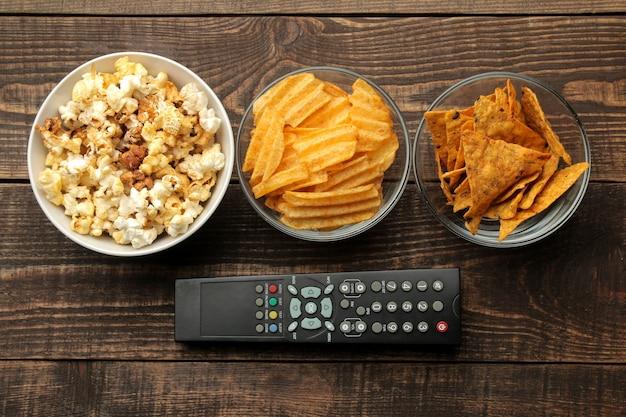 갈색 나무 배경에 토틸라 팝콘, 칩, tv 리모컨이 있습니다. 집에서 영화를 보는 개념. 위에서 보기