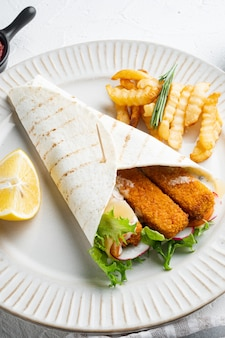 흰색 배경에 접시에 생선 손가락, 치즈, 야채 세트가 있는 토르티야 롤