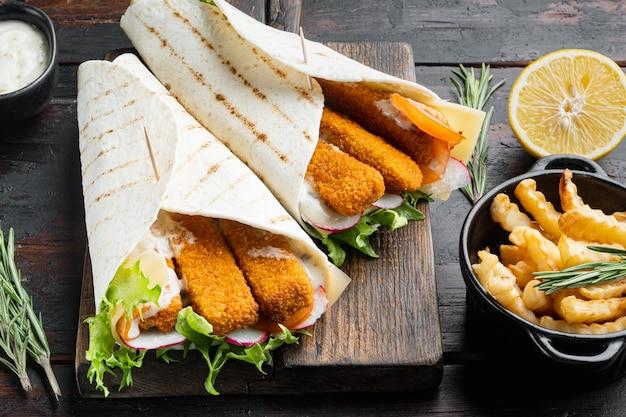 토르티야 롤, 생선 손가락, 치즈, 야채 세트, 나무 커팅 보드, 오래된 어두운 나무 테이블 배경