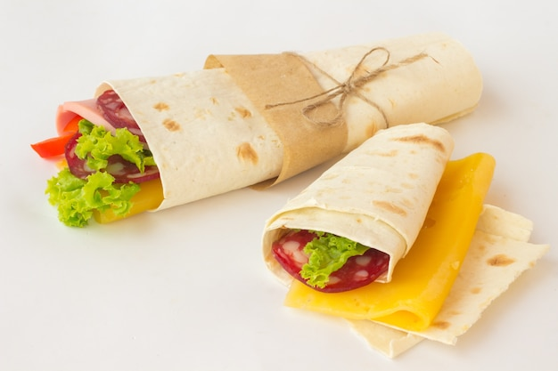 Tortilla rolls with smoked meat and vegetables on a white