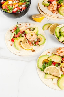 Tortilla tacos with traditional homemade salad, parsley, fresh lemon, avocado and grilled shrimps